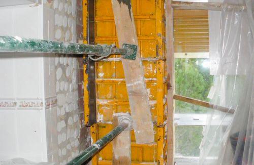 Detalle encofrado y vertido de encamisado de pilar en cocina en edificio de vivienda en Gola de Puchol, Valencia. Obra de refuerzo estructural realizado por personal de Global Home Happiness.